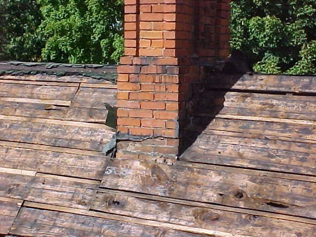 A roof and chimney that needs to be repaired.